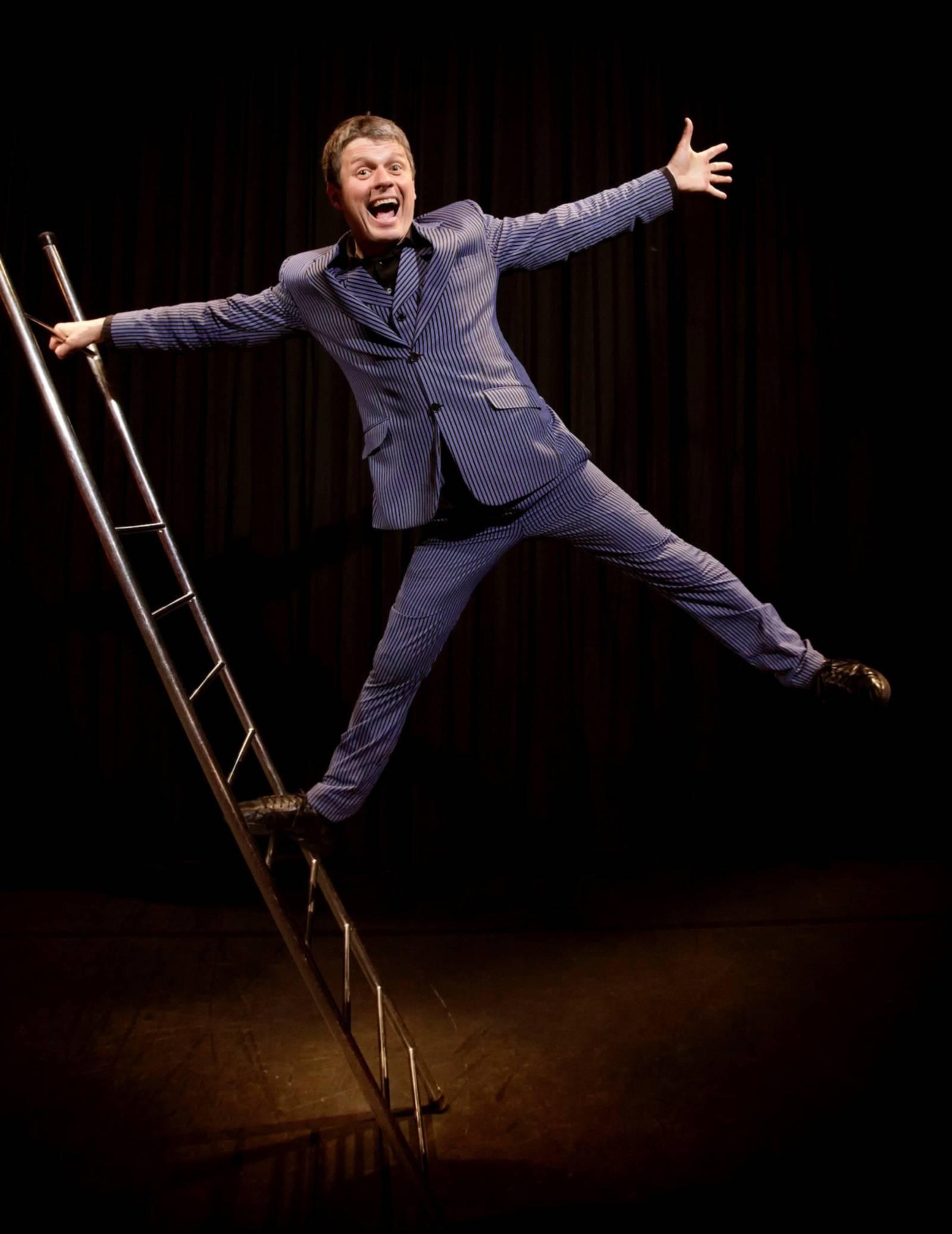 Ein Mann macht Faxen an einer Leiter