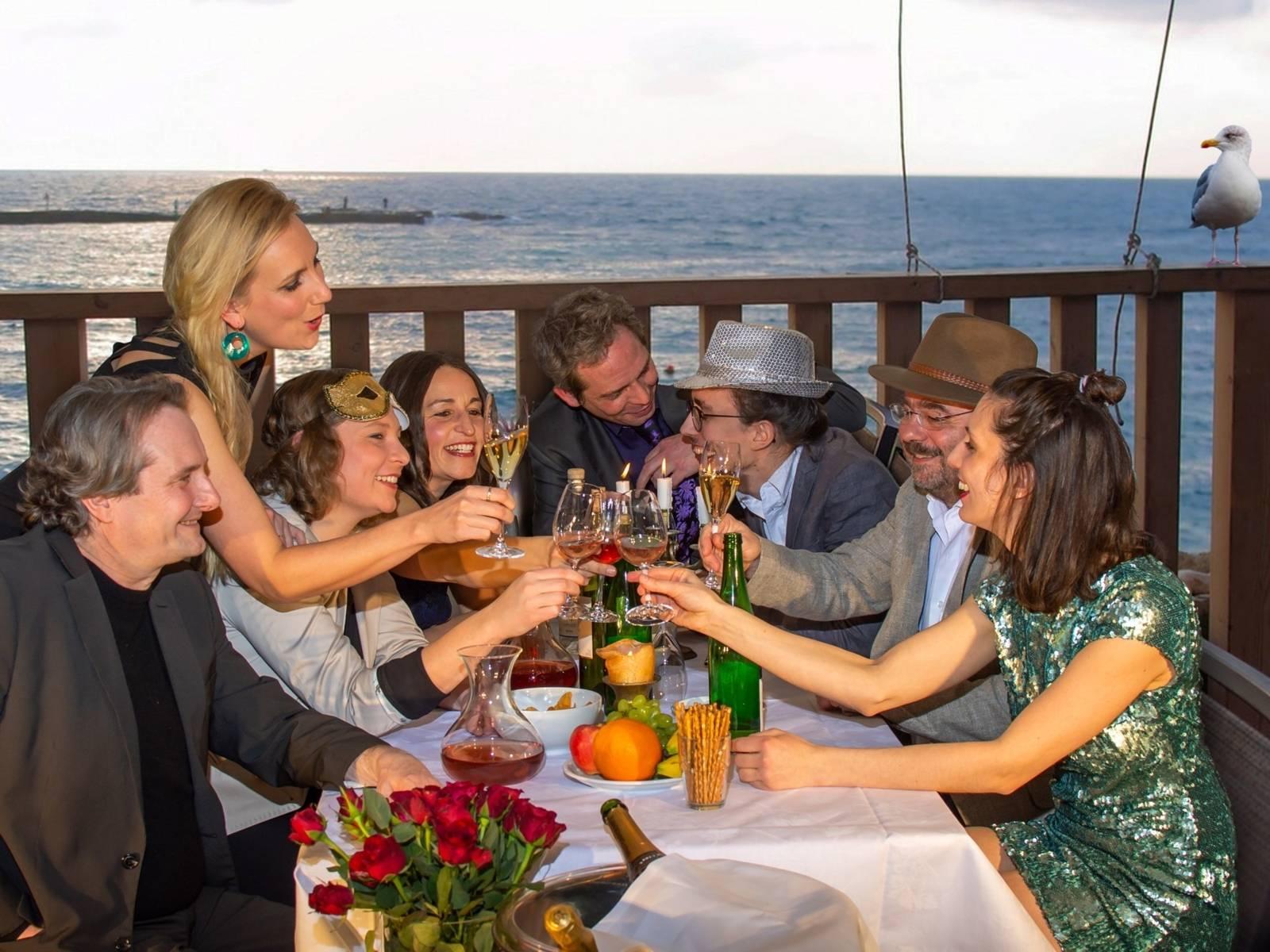 Eine sichtlich vergnügte Gruppe von vier Frauen und vier Männern an einem Tisch auf einer Terrasse am Meer