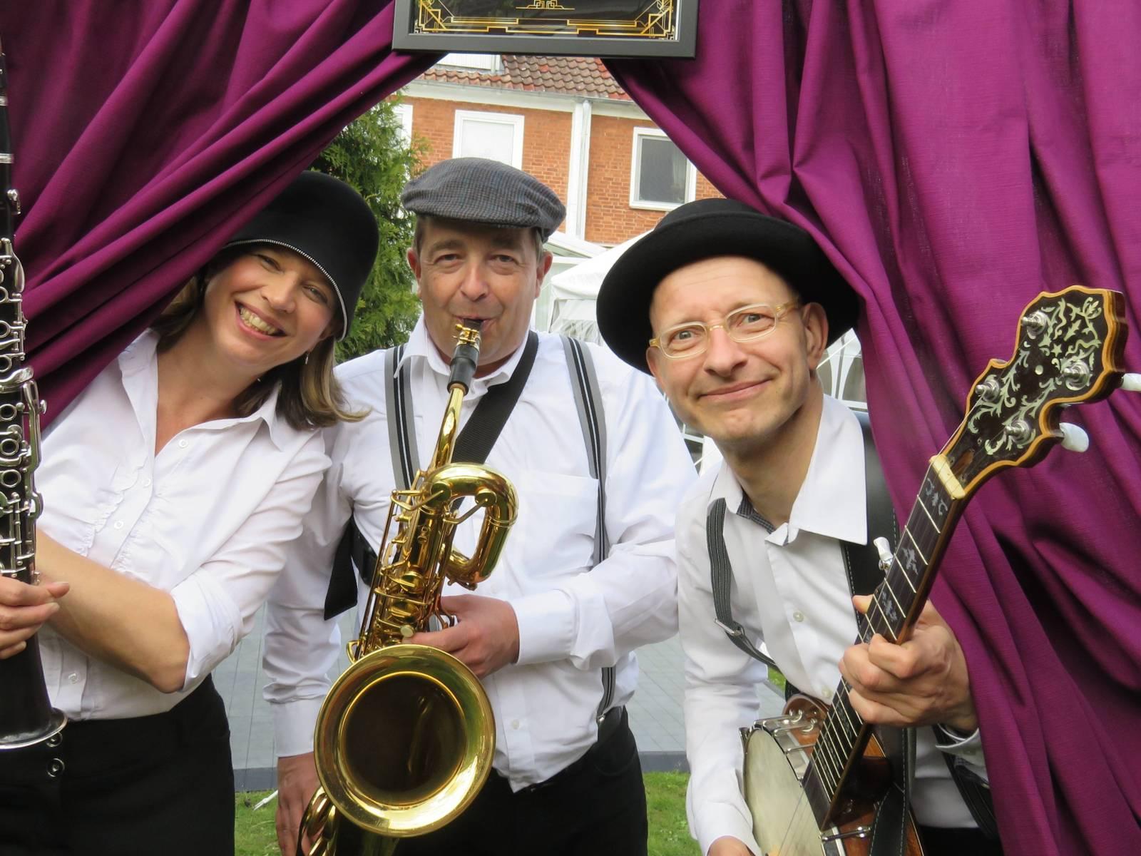 Zwei Musiker und eine Musikerin schauen durch einen Vorhang, die Szene ist in einem Garten.
