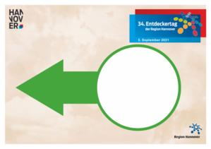 Ein weißer Pfeil zeigt nach rechts. In einen hellblauen Kreis kann die Nummer des Tourenziels eingetragen werden. Der Hintergrund des Pappschildes ist dunkelblau. Außerdem sind Logos auf dem Schild untergebracht, zum Beispiel vom Entdeckertag und der Region Hannover.