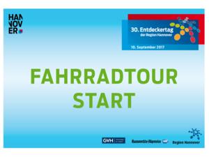 """Schild  mit Text, darauf steht in roter Schrift """"FAHRRADTOUR"""", direkt darunter steht in weißer Schrift """"START"""". Der Hintergrund des Pappschildes ist dunkelblau. Außerdem sind Logos auf dem Schild untergebracht, zum Beispiel vom Entdeckertag und der Region Hannover."""