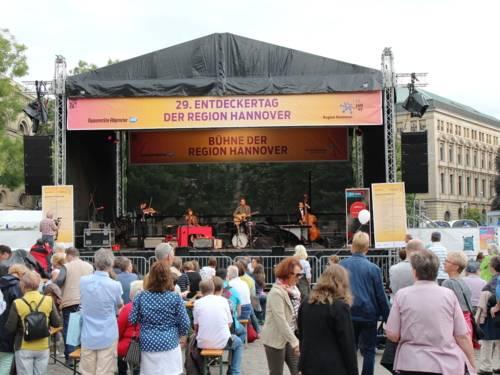 """Musizierende spielen auf einer Bühne, auf einem Banner steht """"29. Entdeckertag der Region Hannover. Bühne der Region Hannover"""". Davor stehen Menschen und folgen dem Bühnenprogramm."""