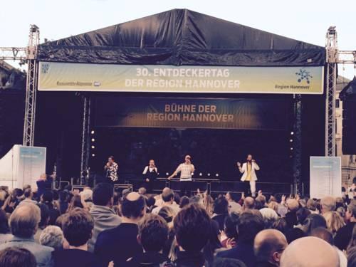 Vier Musiker auf einer Bühne im Freien. Davor stehen viele Leute.
