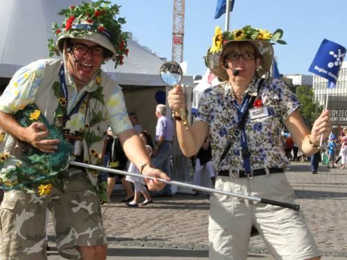 Entdecker und Forscherin alias Pedro Prüser und Susanne Nülle genießen das Entdeckerfest. Der Entdecker spielt auf seinem Kescher Luftgitarre während die Forscherin Lupe und Fähnchen mit beiden Armen in die Luft streckt.