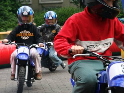 Drei Kinder sitzen auf Minimottorrädern und biegen gerade um die Kurve eines Parcours. Auf dem Kopf tragen sie Motorradhelme.