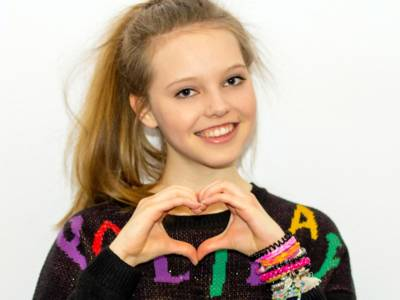 Ein Mädchen lächelt in die Kamera und formt mit ihren Fingern ein Herz.