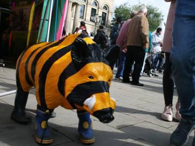 Ein unechtes gestreiftes Wildschwein, das Gummistiefel trägt.