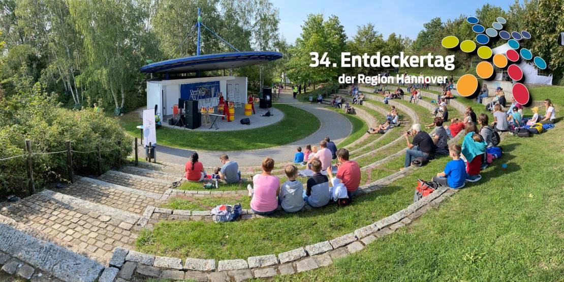 Eine Bühne im Grünen mit vereinzelten Menschengruppen davor