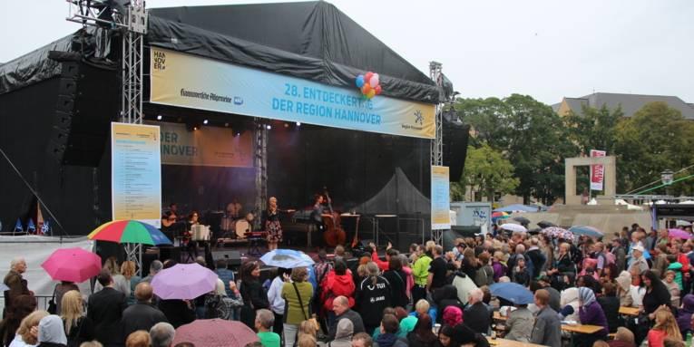 Entdeckerinnen und Entdecker folgen dem Bühnenprogramm, vorsorglich sind einzelne Regenschirme gegen erste Tropfen aufgespannt.