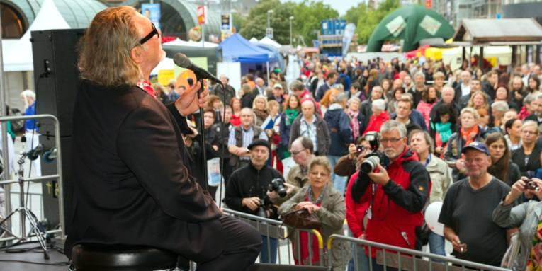 Ein Mann sitzt auf einem Barhocker vor einem Mikrofon, viele Gäste verfolgen den Auftritt. Im Hintergrund sind die Stände der Aussteller des Entdeckertags zu sehen.