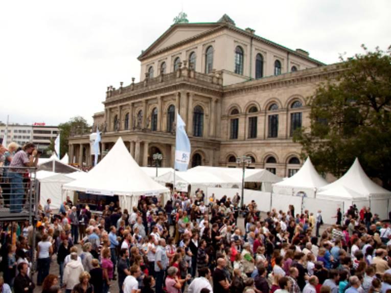 Vor dem Opernhaus in Hannover stehen weiße Pagodenzelte, eine große Menschenmenge füllt den Opernplatz.