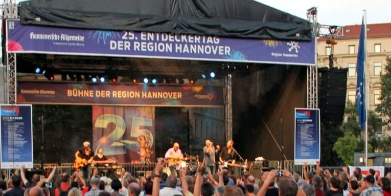 Die Bühne der Region Hannover ist die Hauptbühne beim Entdeckertag, sie steht in der Innenstadt von Hannover auf dem Opernplatz. Auf der Bühne spielen wingenfelder:Wingenfelder, davor drängt sich das Publikum. Die Menschen feiern ausgelassen, einige strecken ihre Arme nach oben und klatschen im Takt der Musik.