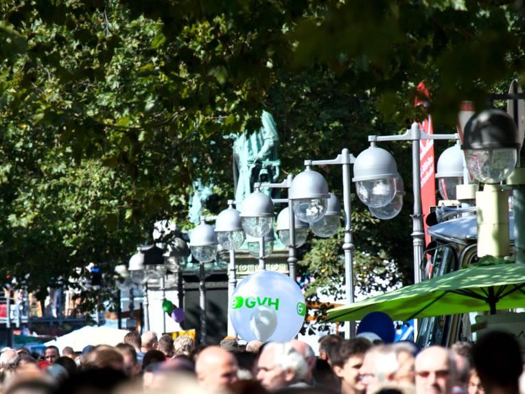 """Zwischen Opernplatz und Georgsplatz drängen sich Menschen entlang der Georgstraße, ein weißer Luftballon mit grünem Aufdruck """"GVH"""" ist gut zu sehen."""