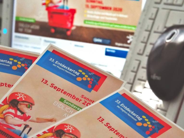 """Programmflyer zum Entdeckertag 2020 als Fächer vor einem Computerbildschirm, einer Tastatur und einer Maus, der Monitor zeigt die Seite """"Programmheft Download & Print"""" auf www.entdeckertag.de"""