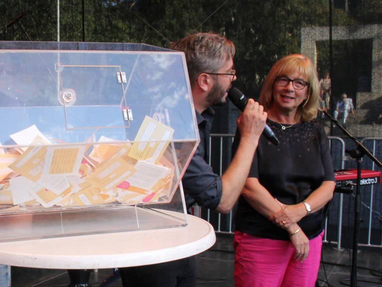 Glücksfee Petra Rudszuck (stellvertretende Regionspräsidentin) mit Moderator Jan Egge Sedelies neben der gefüllten Lostrommel