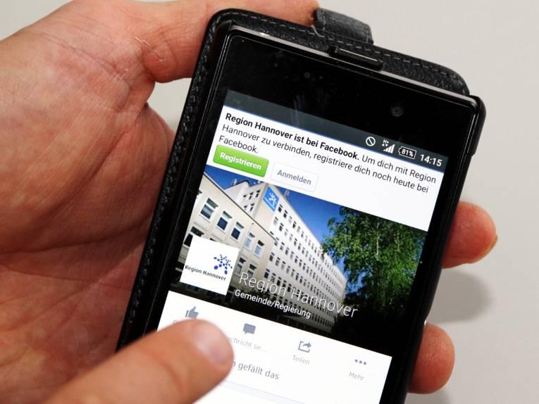 Jemand bedient sein Smartphone und ruft den Auftritt der Region Hannover bei facebook auf: facebook.com/hannoverregion