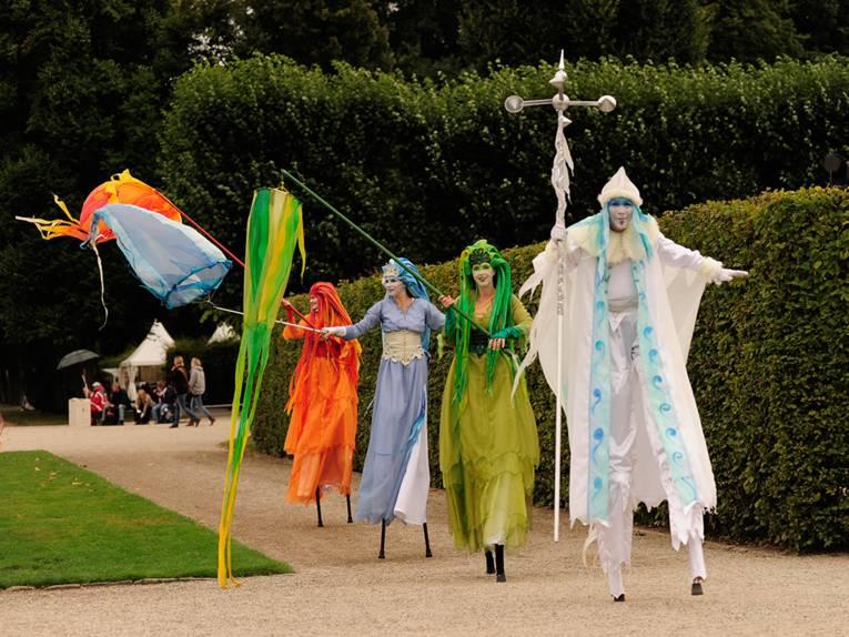 Vier bunte verkleidete Personen auf Stelzen im Großen Garten
