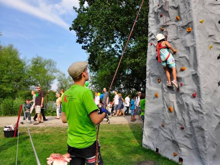 Ein Kind erklimmt einen Kletterberg.