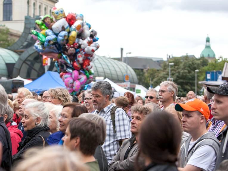Viele Menschen füllen den Platz am Kröpcke, im Hintergrund steigt eine Traube mit bunten Heliumballons in den Himmel.