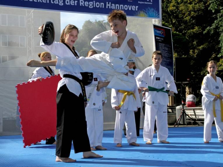 Ein Junge im weißen Kampfsportanzug fliegt durch die Luft und tritt mit dem Fuß gegen einen gepolsterten Handschuh, den eine Trainerin festhält. Im Hintergrund sind weitere Kinder im Kampfsportanzug vor dem Banner der Sportaktionsfläche zu sehen.