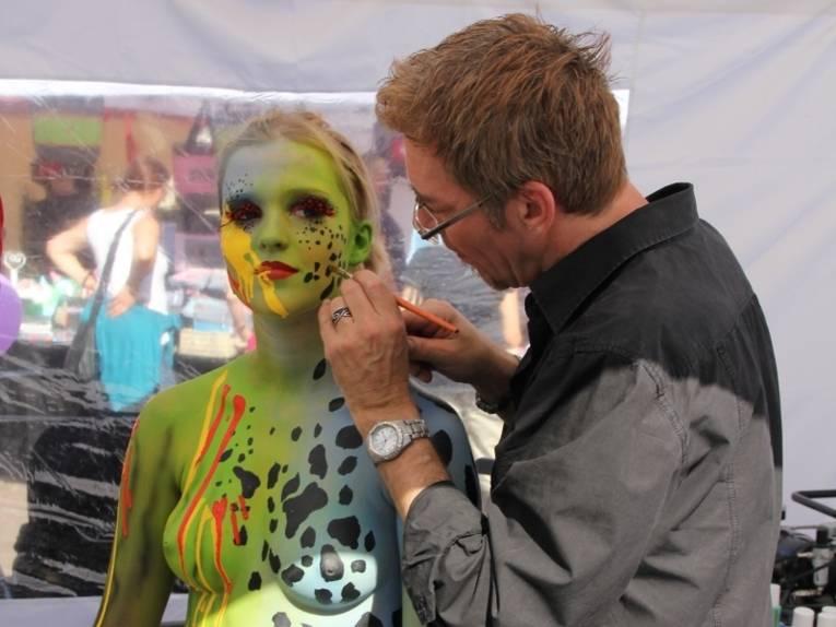 Künstler Jörg Düsterwald bemalt ein Model. Grüntöne herschen bei diesem Body-Painting vor.