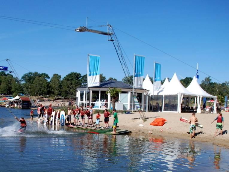 Am Ufer des Blauen Sees hat sich eine Schlange von Menschen gebildet, die auf Wakboard oder Wasserskiern über das Wasser gezogen werden wollen.