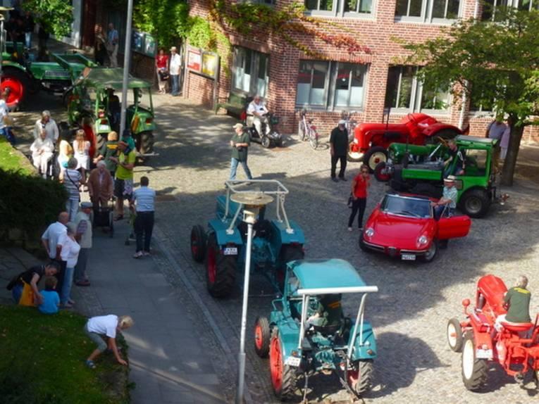 Aufnahme aus der Vogelperspektive: Sieben alte Traktoren und ein roter Sportwagen fahren durch Gehrden, Menschen stehen am Straßenrand und beobachten das bunte Treiben.