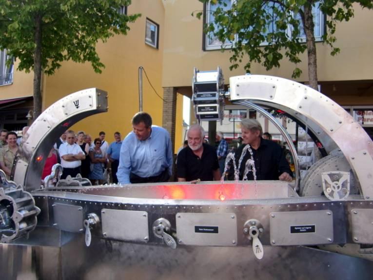 Schmiedekünstler Andreas Rimkus (vorne rechts) führt zahlreichen Gästen den neuen Brunnen am Springer Oberntor vor.