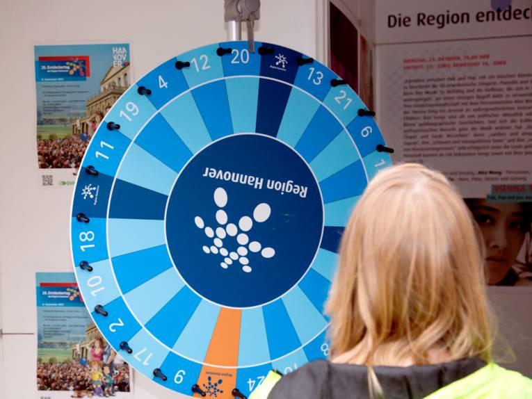 Ein Mädchen steht vor einem Glücksrad. Die Felder des Glücksrades sind überwiegend blau, in der Mitte ist das Punktelogo der Region Hannover.
