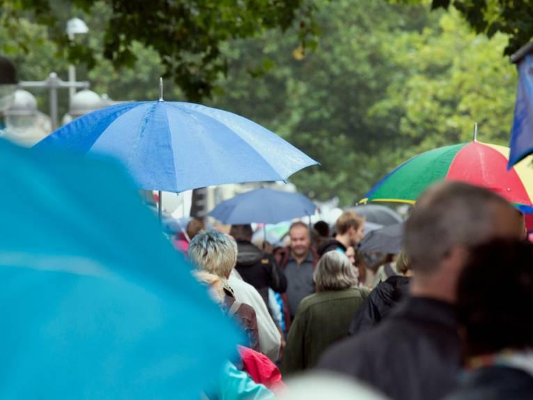 Viele Menschen gehen in Hannover auf dem Fußweg parallel zur Georgstraße, die meisten halten sich einen Regenschirm über den Kopf.
