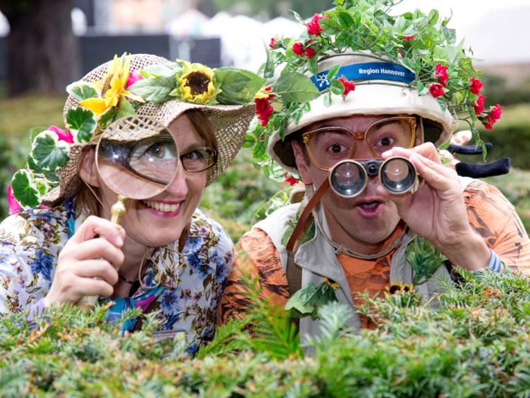 Forscherin und Entdecker alias Pedro Prüser und Susanne Nülle halten Ausschau. Sie benutzt dazu eine Lupe, er ein Fernglas.