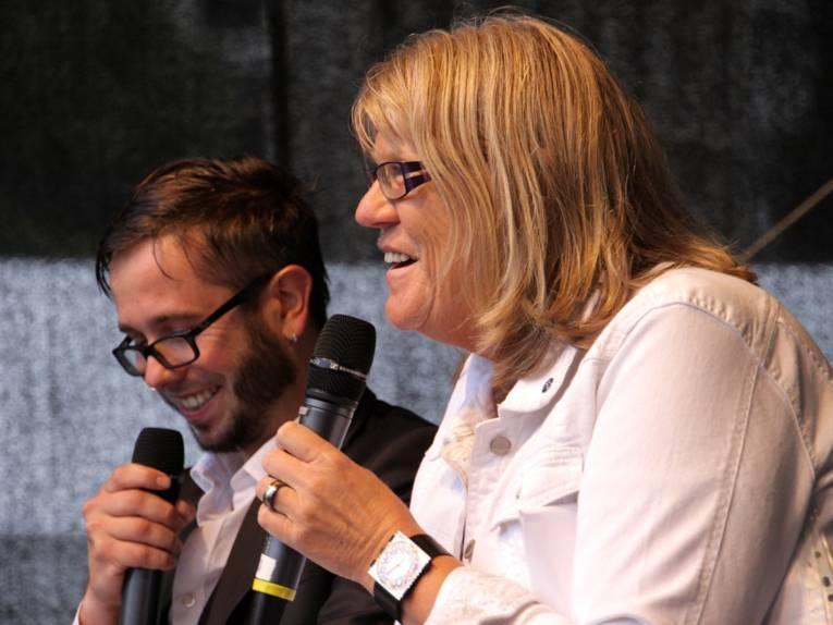 Moderator Jan Egge Sedelies und stellvertretende Regionspräsidentin Angelika Walther vergeben einen der Gewinne bei der Entdeckertagsverlosung.