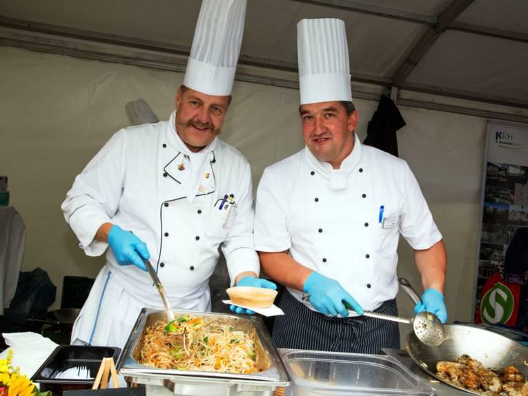 Zwei Männer tragen weiße Kochkleidung und hohe Kochmützen, sie bieten ein Nudelgericht und Scampis aus einem großen Metallbehälter und einer Pfanne an.