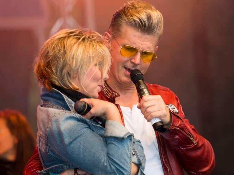 Eine blonde Frau und ein blonder Mann stehen auf einer Bühne, er nimmt sie in den Arm und singt in ein Mikrofon.
