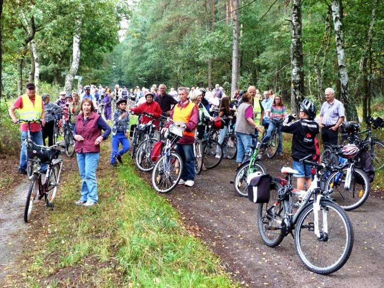 Fahrradfahrer haben ihrer Räder auf und neben einem Waldweg abgestellt, die meisten Leute stehen bei ihrem Rad und blicken in Richtung der Kamera.