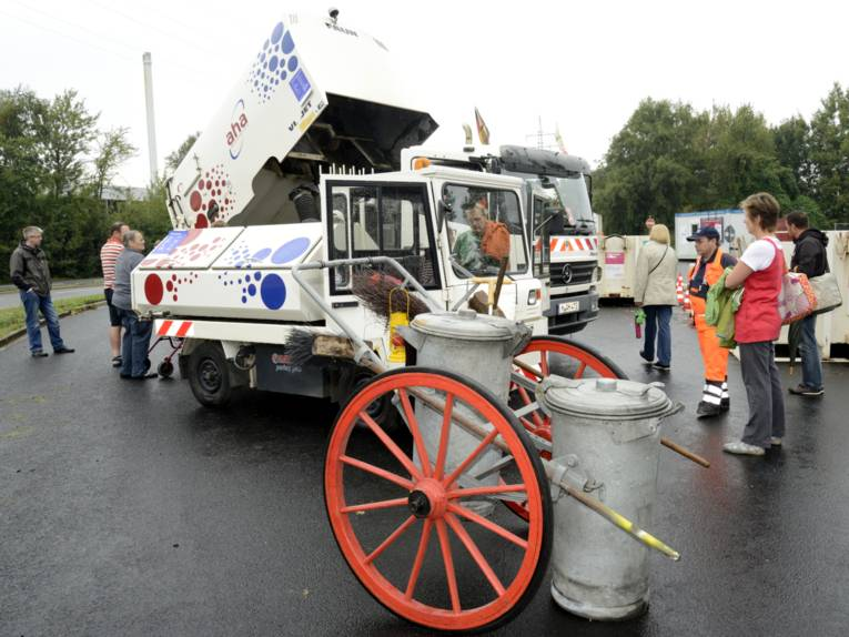 Besucherinnen und Besucher schauen sich einen Kehrwagen und eine kleine und eine große Kehrmaschine der aha-Fahrzeugschau am Fuße des Müllbergs an.