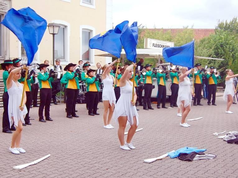 Mädchen der Colorguards tragen weiße Kleider und schwenken blaue Fahnen, dahinter spielt ein Fanfarenzug.