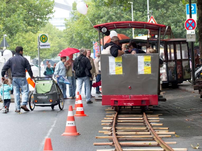 Schienen liegen auf der Georgstraße, eine kleine Lokomotive fährt darauf und befördert Menschen. Auf der Straße sind Fußgänger unterwegs.