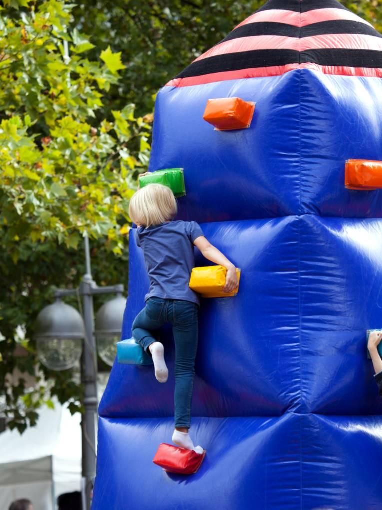 Ein Kind erklimmt ein großes Kletterhindernis