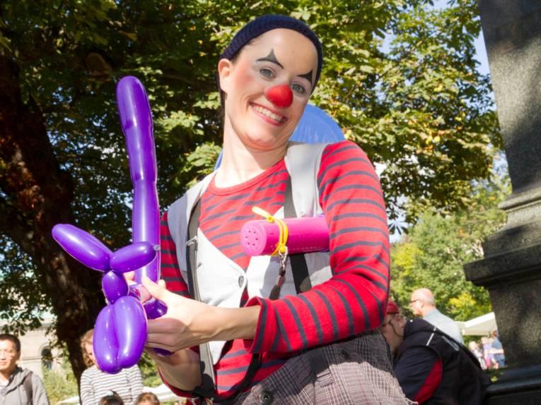 Eine Clownin knotet einen Hund aus einem Luftballon.