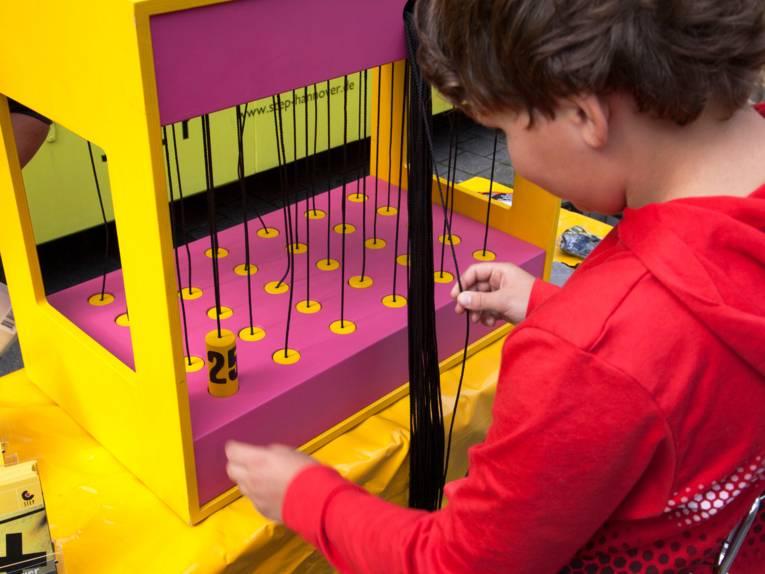 Ein Mädchen sitzt vor einem Spielgerät, an dem Fäden gezogen werden.