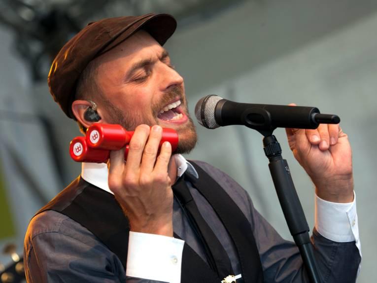 Ein Mann steht hinter einem Mikrofon und singt.