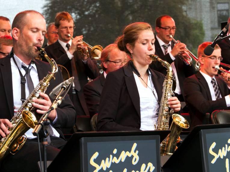 Mehrere Künstler und eine Künstlerin stehen oder sitzen auf einer Bühne und spielen Saxophon oder Trompete.