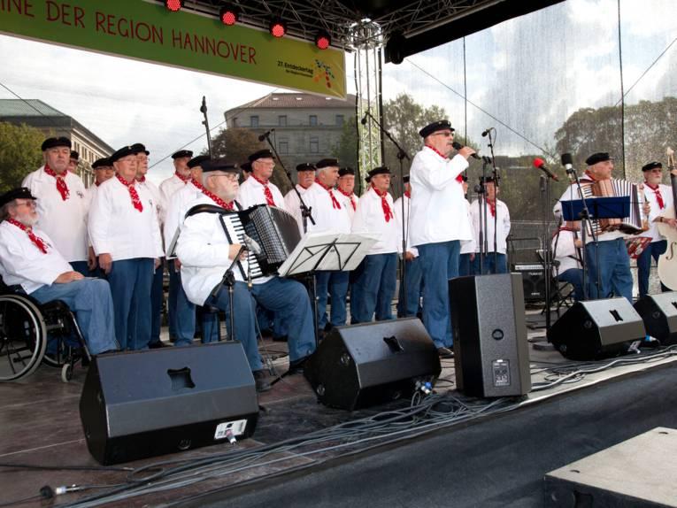Ein Männerchor trägt maritime Kleidung auf einer Bühne.
