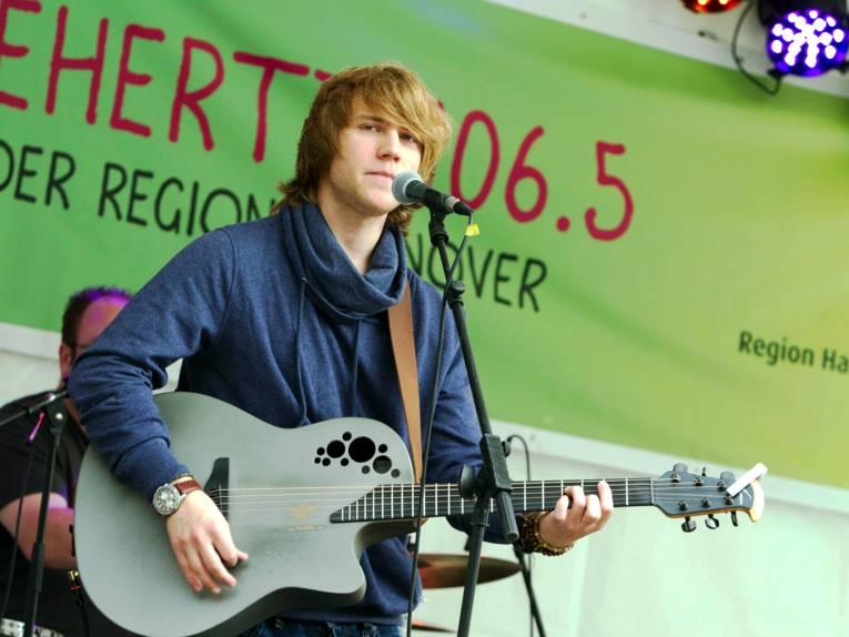 Ein Mann mit einer Gitarre steht hinter einem Mikrofon.