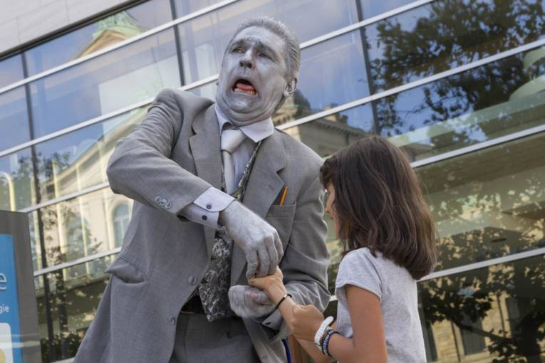 Ein Künstler trägt einen silberfarbenen Anzug und Silberfarbe auf der Haut, er scherzt mit einem Kind.