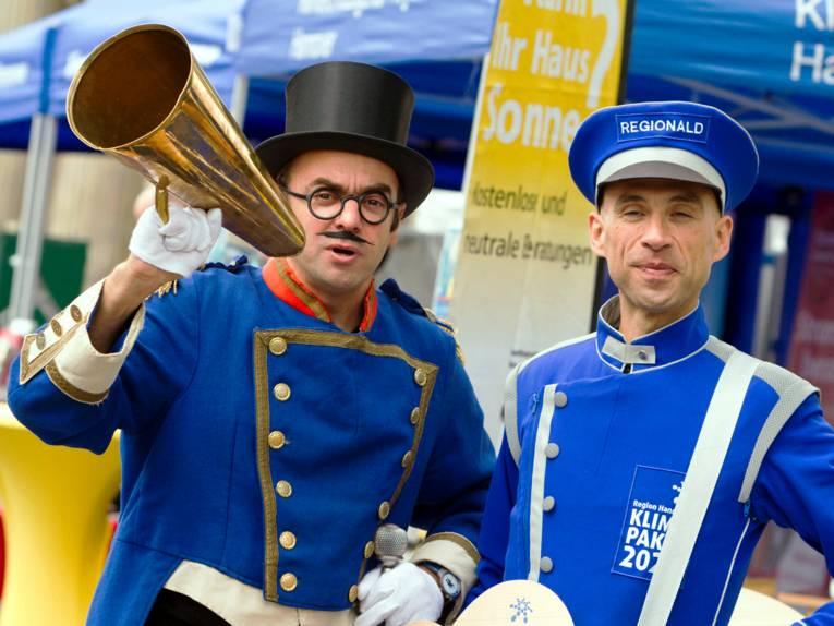 """Zwei Männer tragen blaue Kostüme, auf einer Dienstmütze steht """"Regionald"""", es ist der Klimapaketbote."""