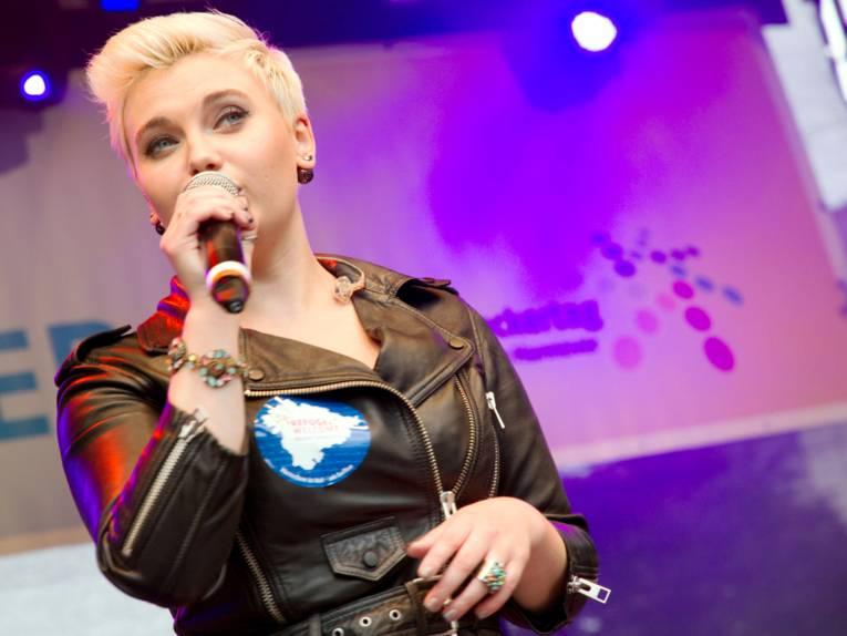 """Frontfrau Elżbieta """"Ela"""" Steinmetz singt auf der Bühne am Opernplatz in ein Mikrofon."""