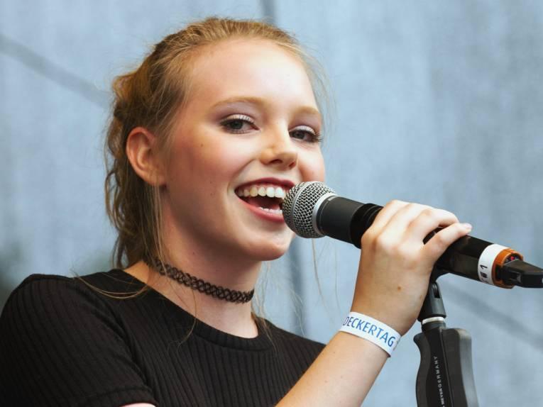 Lina Larissa Strahl singt in ein Mikrofon und blickt in die Kamera