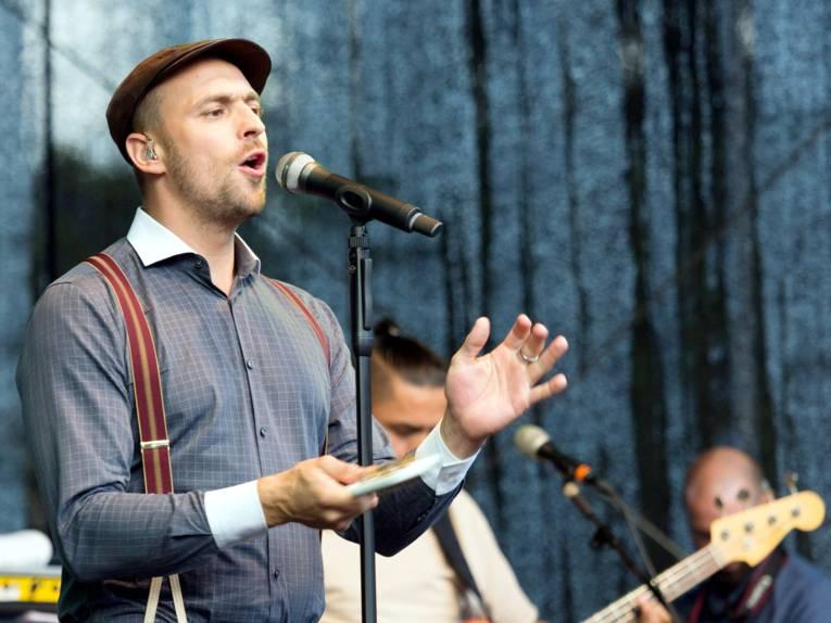 Max Mutzke singt in ein Mikrofon.